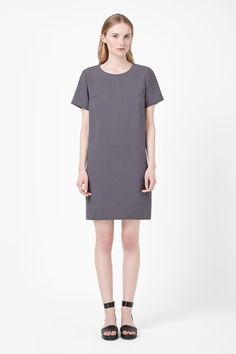 A simple straight-cut shape, this dress has a clean round neckline and neat short sleeves. Made from a lightweight fabric with a soft matte finish, it is a loose fit with a partial back zip fastening and cleanly finished edges.