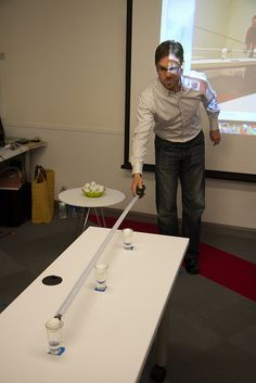 Ping pong balls rolled down a tape measure into cups.