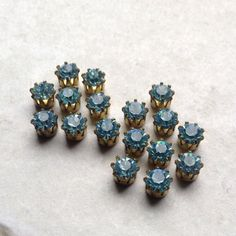12 vintage sparkling pale blue stones set into pronged brass.  These small stones measure 5mm at the top and 3mm at base (3/16 and 1/8)  These have flat backs and are perfect for making collage style jewelry.  Made in the USA, 1960s.  12 per lot  I ship worldwide from the UK and charge a flat rate shipping of £1.50 in the UK and £3.50 worldwide, meaning no matter how large your order, the shipping cost stays the same.