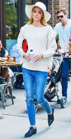 Jaime King wears a white fringe sweater, skinny jeans, oxfords, a felt hat, and a red clutch