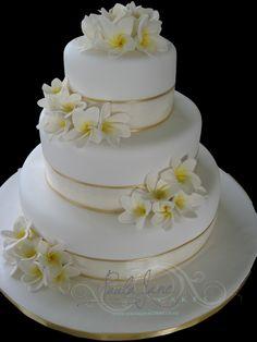 Sugar frangipanis and cream and gold ribbon