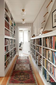Hallway: built-in bookshelves, frosted schoolhouse lights with gold base