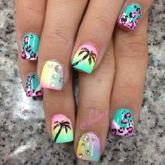 Animal inspired Palm Tree Nail Art design. The nails have tons of designs on them that make it look exciting and fun. You can see that the silhouette of the palm tree is painted on a rainbow inspired background.