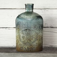 Inspired by antiqued European stylings, this lovely bottle is brimming with chic style. The perfect accent for any aesthetic, this bottle will take your tabletop space from simple to showstopping. Showcasing an antiqued mercury aqua finish, a mouth blown artisans-finished design, and a medallion etched accent, this decor is a must-have for your home. Set this eye-catching glass bottle on your entryway console for a pop of intriguing style. Then try adding a mirrored tray, blooming bouquet of…