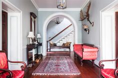 """A gorgeous wide open hallway leads to the main staircase and is  painted a soft pale dove gray and edged in intricate, classical millwork and mouldings. Bright pops of red -- in the forms of a vintage Persian rug, matching upholstered red silk arm chairs and a stunning scroll-arm day bed -- add a perennial festive touch, as does moose antlers above. See fine-jewelry designer Elizabeth Locke's full home tour in """"A Stunning Estate with Southern Grace and Italian Romance"""" over on our Style…"""