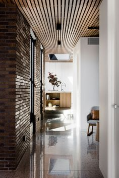Elongated brown brick, which is a reminder of this once working class suburb, features on both the exterior and throughout the interior of this modern house, like in the entryway.