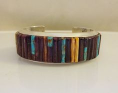 VINTAGE NAVAJO CORNROW INLAY BRACELET  DESCRIPTION: This exquisite cuff features tightly constructed cornrow inlay of…