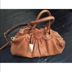 """Marc by Marc Jacobs Q Grovee Satchel This is the classic Marc by Marc silhouette is the perfect color. Goes with everything, big enough to fit everything, yet small enough that you aren't lugging around a suitcase. Beautiful cognac tan leather and all of the fun Marc details! Originally $498, the bag has two top handles and a long shoulder strap, top zipper closure, an interior pocket with zip closure, and two interior slip pockets. Bag dimensions are 15 1/4""""W x 10 3/4""""H x 8 1/2""""D. 7"""" handle…"""