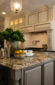 Antique ivory kitchen cabinets with blacK & brown granite countertops and coordinating island paint.