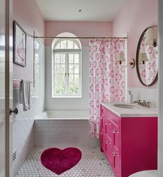 Lovely, pink girl's bathroom features a pink heart shaped bath rug placed on white marble honeycomb floor tiles in front of a hot pink washstand accented with glass knobs and a honed white marble countertop holding a round sink beneath a polished nickel cross handle faucet kit.