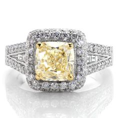 Design 2275 - A magnificent halo design enveloped with micro pavé, this ring glimmers and shines from every angle. The center is a 1.50 carat fancy yellow cushion cut diamond set with an accent of yellow gold prongs. Channel set baguettes rest in the middle of the micro pavé. The design is framed with milgrain edges.
