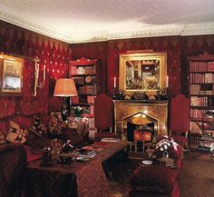 Renzo Mongiardino ~ sitting room has a gilt-bronze chimneypiece designed by Mongiardino, flanked by a pair of English chairs, circa 1685.    Bookcases are painted a red tortoiseshell finish against upholstered silk velvet walls with appliqued paisley motifs.