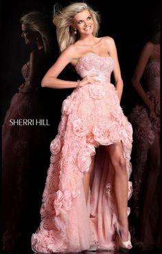 Sherri Hill 21170 is a twist on the girly Sherri Hill classic ballgown with rosettes- this gown has the ever popular high low hem!!  Perfectly feminine but also fun and flirty, this dress is sure to stand out at your prom, pageant or formal event!  We love this dress and so will you, from the semi sweetheart neckline, to the cinched satin waist band, to the fully embellished skirt, this dress is fabulous!  We are in love!