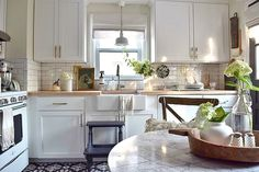 Love this small white kitchen with gold hardware and marble top table eclecticallyvintage.com