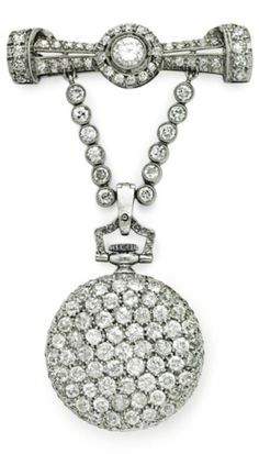 A BELLE EPOQUE DIAMOND LAPEL WATCH, BY TIFFANY & CO, CIRCA 1910. With mechanical movement, the white circular dial with gold Arabic numerals, within a circular-cut diamond case, to the rose-cut diamond winding stem and old-cut diamond hoop, suspended from the old-cut diamond brooch, 2 1/4 ins., mounted in platinum, signed Tiffany & Co. #Tiffany