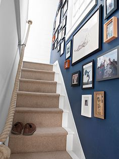 A nautical rope lends a hand as a witty alternative to the standard banister, while family photos and an eclectic art collection line the stairwell. - I like the photo grouping here.