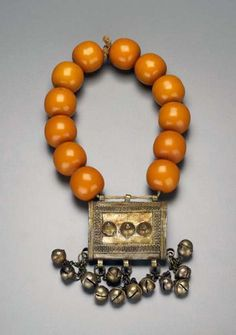 Africa | Necklace with amulet case from the Somali people of Mogadishu. Silver alloy, synthetic amber beads and plant fiber. | ca. mid 20th century | Most of the silver- and goldwork on the Somalian coast is done by a guild of silversmiths and goldsmiths considered an artisan caste.