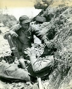 "Okinawa, May 1945  The caption on this photograph reads ""My Buddy-A Marine comforts a brother Leatherneck who broke down and cried after witnessing the death of a buddy on an Okinawa hillside. These First Division Marines participated in the furious drive on Shuri Castle the enemy fortress two miles east of the capital city of Naha."""