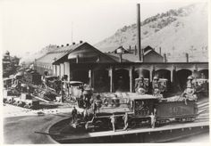 A narrow-gauge train had arrived from the west, a locomotive (possibly No. 218) was removing the loaded gondolas of ash from next to the ashpit, and No. 404 had moved out of the roundhouse onto the turntable. During the warm weather, locomotives under steam were spotted with their stacks outside of the roundhouse to improve ventilation in the building.  Walter Moore is pictured in the center of three men leaning against No. 404.