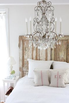 This is pure rustic elegance! The weathered headboard and linen flour sack pillow cases add a touch of country charm to this all white bedroom. I love the juxtaposition of the crystal chandelier and the weathered wood.