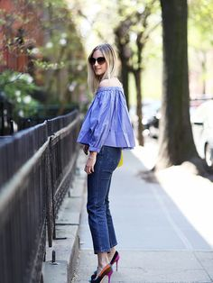 A blue off-the-shoulder shirt is worn with jeans and colorblocked pumps