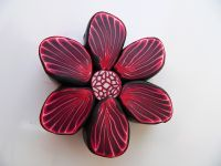 Nice flower cane by Czech artist.  I like the bit of bleeding from the color into the translucent in this case and the subtle color gradients.