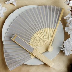 Asian Silk Folding Fans - Silver | eFavorMart / Add a classical Asian touch to your wedding, or a special event by presenting your esteemed guests with this special souvenir. Our stylish silk wedding hand fan is intricately handcrafted with a bamboo structure. The framing and spines are crafted from hand-picked bamboo and durably glued with a seamless cut piece of silk to fashion this immaculate magnum opus. Give these swish fans to your respected guests and let them create the lasting…