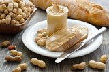 Peanut cream butter on a piece of bread and peanuts