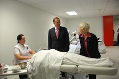 Prime Minister John Key and Principal Catherine Wouters discuss the facial massage Katrina is giving Amy.