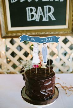 simple chocolate frosted wedding cake with paper banner topper