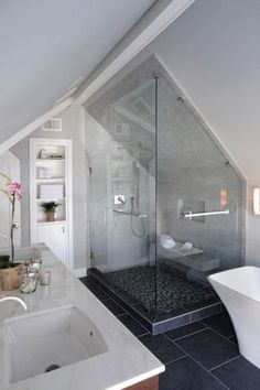 Slate floor, glass shower, freestanding white tub in this attic bathroom.