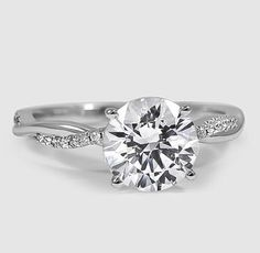 This beautiful ring features a strand of diamonds entwined with a high polished ribbon of white gold.