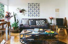 Sala de estar em tons neutros com sofá cinza e painel de azulejos da marca Lurca.