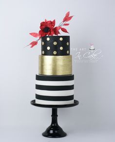 Kate Spade Cake.  3 tiers: Black with gold dots, gold luster and bottom tier black and white stripes in fondant.  Topped with Red Anemone sugar flower and wafer paper leaves.  #StLouisCakes #KateSpade #GoldCake #PolkaDotCakes #Cakes #CakesOfPinterest #Stripes #BlackAndWhiteCake #3TierCake #Anemone #FlowerCakeTopper