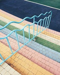 Blue wavy railing and pastel stairs.