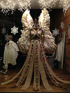 Christmas window display with paper plate angel wings burlap gown and ball garland trim!