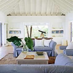 large banana leaves are arranged in a glass vase on the coffee table with a white couch situated behind