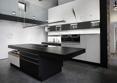 reforma cocina moderna en vivienda rehabilitada con isla central para zona de cocción y pequeña barra, cerramiento parcial con muebles y electrodomésticos, suelo microcemento.