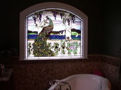 stained glass windows in the bathroom allow light and a focal point to a space