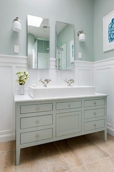 source: Templer Interiors website save: share: White and green bathroom features top half of walls painted green and lower half of walls clad in board and batten lined with a green washstand topped with white marble and a white porcelain trough sink paired with his and her faucets under separate tall vanity mirror illuminated by white glass downlight sconces.