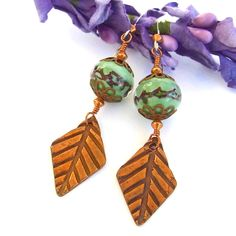 Looking like a breath of refreshing fall air, these gorgeously lush autumn inspired earrings will dance from your ear. The AUTUMN ARIA handmade earrings were created with artisan made copper diamond-shaped leaf charms glowing green lampwork beads. The lampwork beads were complemented with copper filigree bead caps and copper bicones.