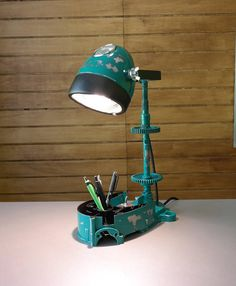 I made this table lamp/pencil holder from old motorcycle parts. I used engine block, gearbox parts, mileage clock.  The painting of the lamp is unique. To get the shabby look,after the painting i burnished the parts than i added a lacquer layer.  The head of the lamp can be adjusted to up and down and every directions as well.  The black cable is approx. 1,5 m long.  The LED bulb has G10 socket.  The height of the lamp is approx: 45 cm.   Additional informations:  - The lamp was made in ...