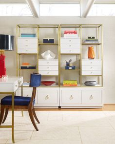 Interesting bookshelf combines filing cabinets, drawers, and shelving in classy white wood and gold. The perfect addition to any home office to organize with a styled display.