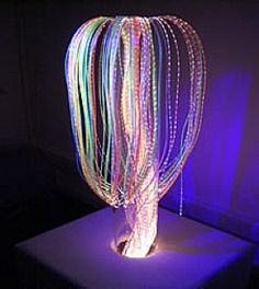 I am going to try a DIY version of this using Mardi Gras type bead strings, a cardboard tube, cardboard box base, glue, blacklight sensitive paint, and a small blacklight