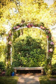 Decorated with vines, garland and fresh floral this arch is perfect for an outdoor setting.