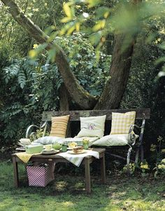 Create a quiet sitting area by placing a bench and table under a shady tree.