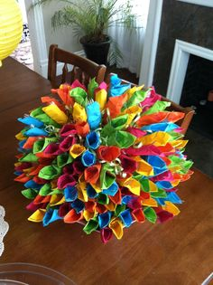 Made this for my sons Mexican themed grad party. I used a large wide bowl for base. Wrapped clear plastic ware in festive colors & started laying them around edge of bowl & built it up. There r 250 wrapped napkins in this pic. Useful & decorative all in one!