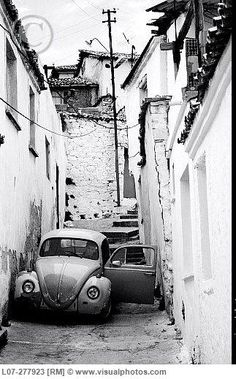 Old Volkswagen Beetle with open door in small white alley. Kusadasi.