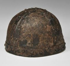 Viking Iron Bremen Style Helmet, 8th-9th century AD A substantial iron helmet formed with a vertical band to the brow, with two flat bands across the skull and triangular plates behind; the bands with domed rivets in pairs across the skull, single...