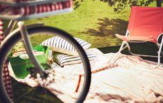 Una tovaglia, dei cuscini e una sedia disposti per un picnic - IKEA